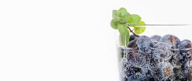 Mirtilos em um copo de água copie o espaço