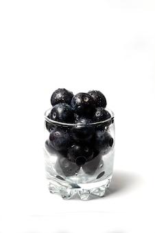 Mirtilos em um copo de vidro isolado no branco