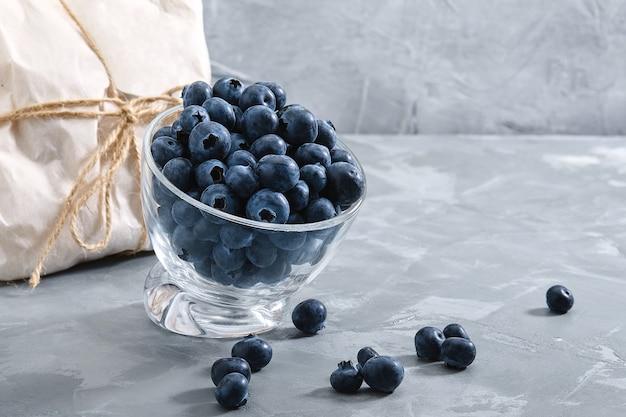 Mirtilos em um fundo preto, baga fresca em uma tigela sobre um fundo de concreto com um envelope embrulhado com uma baga. cópias do espaço, entrega de frutas.