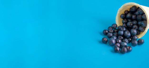 Mirtilos em uma xícara de sorvete waffle em um fundo azul brilhante. super vitamina mirtilo. sorvete vegetariano. bandeira