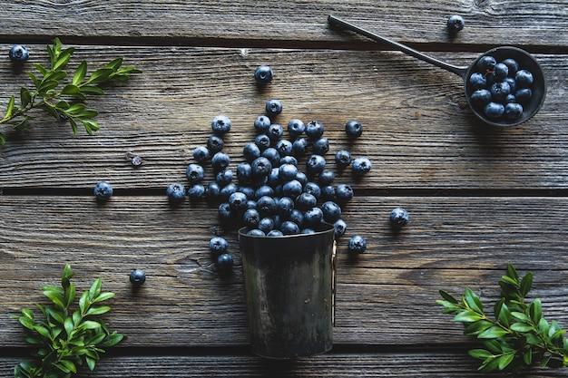 Mirtilos em uma xícara em um fundo de madeira. verão e conceito de comida saudável.