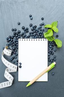 Mirtilos, folhas de hortelã e bloco de notas para escrever notas