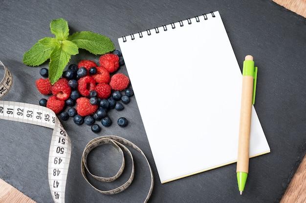 Mirtilos, framboesas, hortelã, fita métrica e bloco de notas para escrever notas