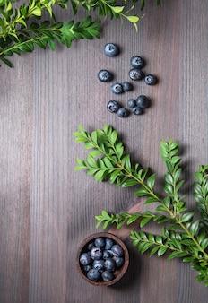 Mirtilos frescos doces em uma tigela com brunch verde sobre um fundo de madeira. vista superior e cópia da imagem do espaço