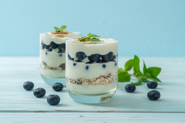 Mirtilos frescos e iogurte com granola - estilo de alimentação saudável