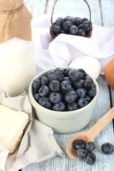 Mirtilos frescos e produtos lácteos na mesa de madeira