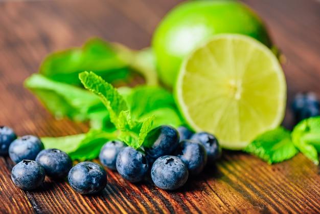 Mirtilos frescos, metade das folhas de limão e hortelã. ingredientes para preparar água com sabor.
