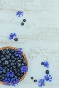 Mirtilos frescos na cesta com vista superior do padrão de flores. comida saudável na mesa branca simulada. baga deliciosa, doce, suculenta e madura, com espaço de cópia para o texto