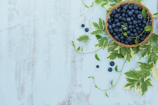 Mirtilos frescos na cesta com vista superior do padrão de folhas. comida saudável na mesa branca simulada. baga deliciosa, doce, suculenta e madura, com espaço de cópia para o texto