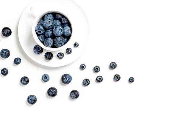 Mirtilos maduros em uma xícara branca e um padrão de frutas vermelhas em um fundo branco vista superior plana lay cópia espaço foco em mirtilos em uma xícara