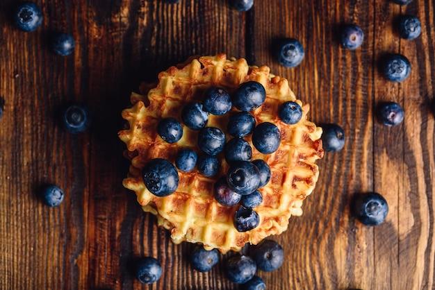 Mirtilos no topo do waffle e outros espalhados no fundo de madeira.