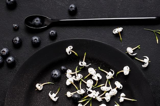 Mirtilos plana leigos na placa escura com flores