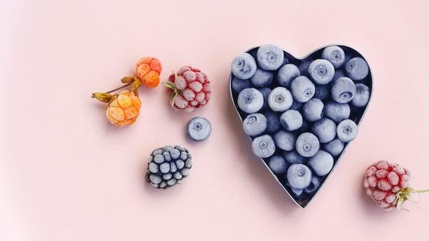 Mirtilos recém-congelados em forma de coração de metal, framboesas, amoras silvestres e amoras silvestres em um fundo rosa. colheita de bagas de verão. espaço para texto