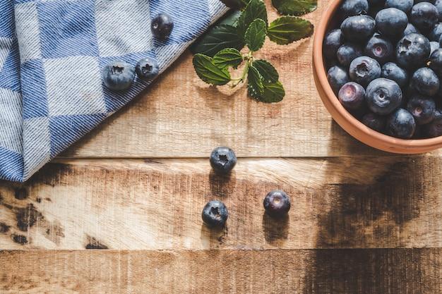 Mirtilos suculentos em uma tigela com tecido azul e mirtilos espalhados em uma superfície de madeira Foto Premium
