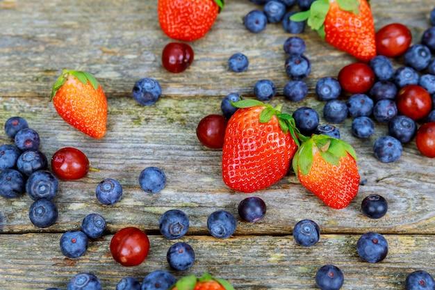 Mirtilos uvas morangos frutas na placa de madeira com fundo de madeira