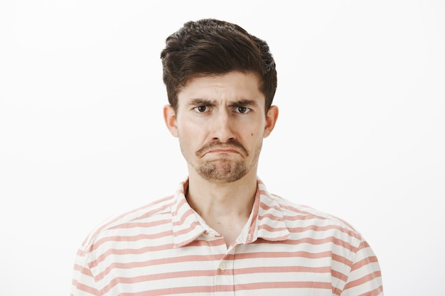 Miserável, triste e atraente irmão europeu com bigode e barba, sentindo-se ofendido e chateado, expressando tristeza e emoções negativas