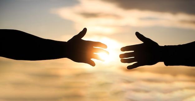 Misericórdia, silhueta de duas mãos no fundo do céu, conexão ou conceito de ajuda.