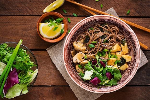 Miso e sopa de macarrão soba com tofu assado e cogumelos. vista do topo