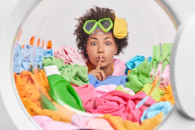 Misteriosa e ocupada dona de casa encaracolada faz gestos silenciosos surpreendentemente olhando para a frente presa na roupa suja usando óculos de mergulho posa na porta da máquina de lavar