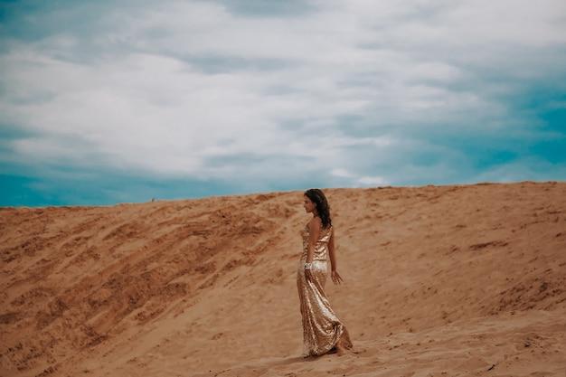 Misteriosa mulher com vestido de ouro andando na areia dourada das dunas do deserto ao pôr do sol