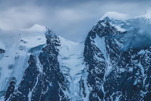 Misteriosa paisagem alpina dramática com o topo de uma montanha de neve dentro de nuvens baixas ao entardecer.