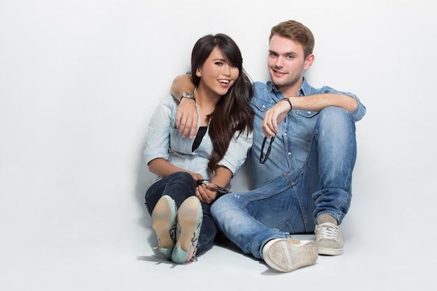 Misto casal sentado no chão. homem mulher abraçando