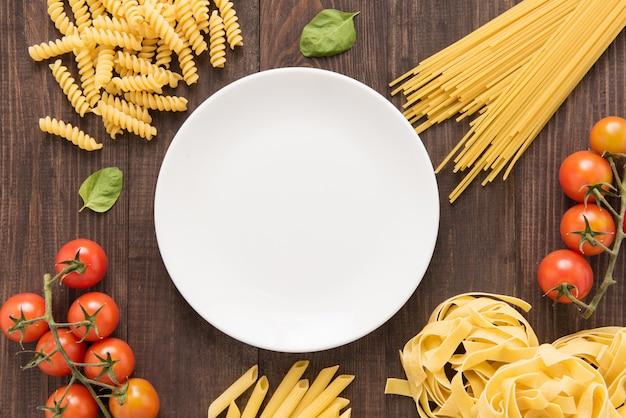 Misto de massas secas e tomate na mesa de madeira