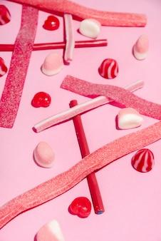 Mistura colorida de doces e pirulitos de açúcar rosa e vermelho
