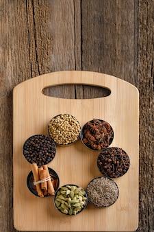 Mistura colorida de especiarias diferentes em uma placa de madeira