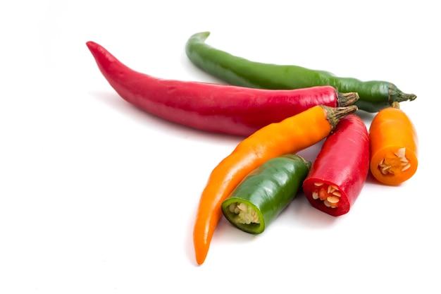 Mistura colorida de pimentas de pimentão no fundo branco.