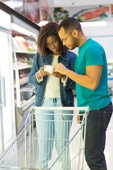 Mistura corrida casal lendo o texto no pacote de alimentos