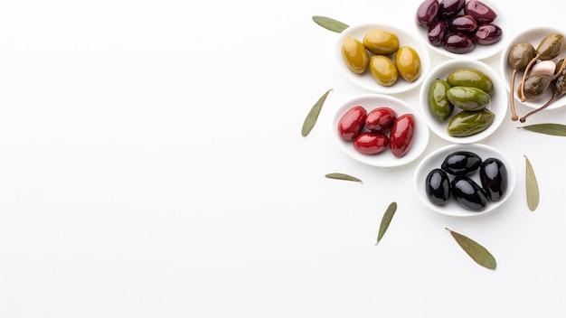 Mistura de azeitonas pretas roxas verdes vermelhas amarelas e óleo com espaço de cópia