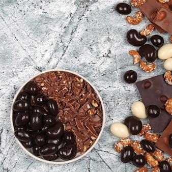 Mistura de barras de chocolate quebradas, raspas de chocolate, caju doce e nozes cobertas de chocolate em fundo de pedra cinza. vista superior com espaço de cópia