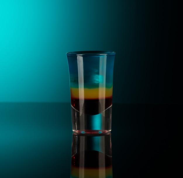 Mistura de bebidas alcoólicas em um copo isolado em um fundo escuro com luz de fundo