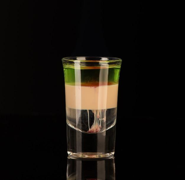 Mistura de bebidas alcoólicas em um copo isolado em um fundo preto