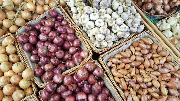 Mistura de cebola bulbo em cestas de venda no balcão do mercado