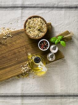 Mistura de cereais em uma tigela de madeira sobre uma tábua com azeite, pimentão colorido e especiarias. comida caseira na toalha de mesa de linho