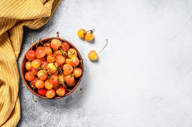 Mistura de cerejas maduras amarelas e vermelhas em uma tigela na mesa branca.