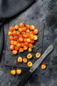 Mistura de cerejas maduras amarelas e vermelhas na mesa preta.