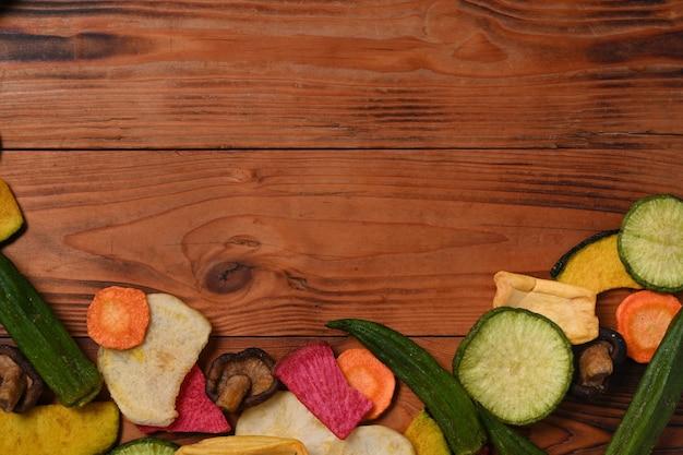 Mistura de chips de legumes secos com cogumelos quiabo, cenoura, abóbora, beterraba e shiitake em fundo de madeira. copie o espaço.