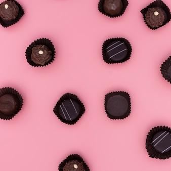 Mistura de chocolates em fundo rosa