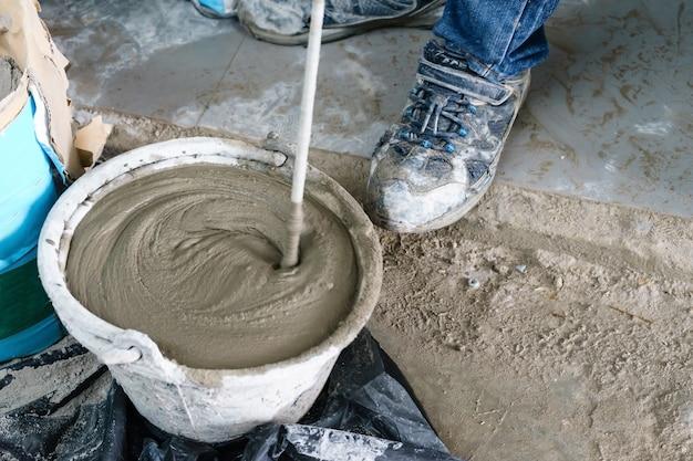Mistura de cimento com um misturador em um balde na rua
