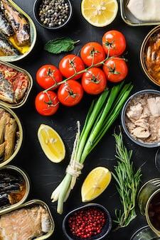 Mistura de conservas enlatadas em latas com ingredientes orgânicos frescos, tomate e ervas de limão no quadro negro. conceito de vista superior.