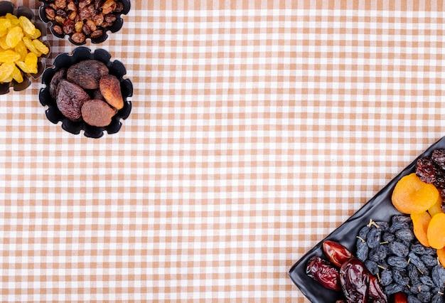 Mistura de datas secas de frutas passas damascos e cerejas em uma bandeja preta e em latas de mini torta na toalha de mesa xadrez com vista superior do espaço da cópia
