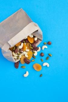 Mistura de diferentes nozes e damascos secos em um saco de papel no fundo azul. lanche saudável. vista do topo.
