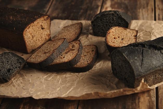 Mistura de dois pães caseiros rústicos, carvão preto e centeio marrom com figos, fatiados em papel artesanal isolado em mesa de madeira