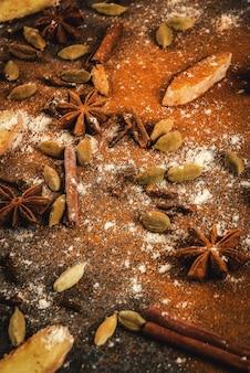 Mistura de espiões moídos secos para chá picante quente ou indiano masala chai canela, anis, cardamomo, gengibre, em uma mesa de mármore branco, pimentão, pimentão, curry, açafrão, gengibre.