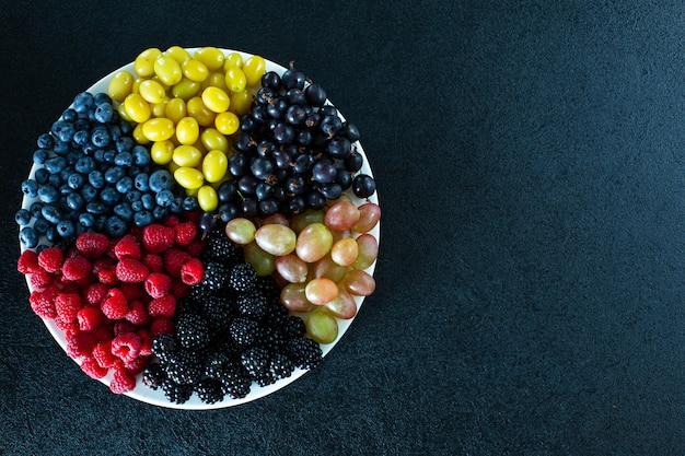 Mistura de frutas coloridas em um prato redondo dividido por triângulos. layout elegante de vitaminas úteis de frutas de verão.