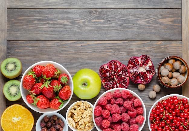 Mistura de frutas, nozes e frutas frescas. a alimentação saudável contém muitas vitaminas e oligoelementos úteis. fundo de madeira marrom. copie o espaço.