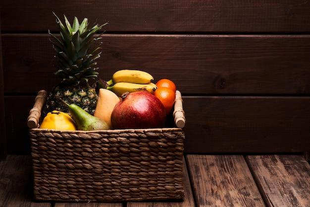Mistura de frutas tropicais exóticas coloridas suculentas frescas em uma cesta com fundo de madeira